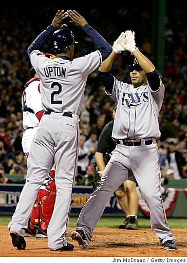 BOSTON - OCTOBER 16:  Carlos Pena #23 of the Tampa Bay Rays is congratulted by teammate B.J. Upton #2 after Pena hit a 2 run home run against the Boston Red Sox in the third inning of game five of the American League Championship Series during the 2008 MLB playoffs at Fenway Park on October 16, 2008 in Boston, Massachusetts.  (Photo by Jim McIsaac/Getty Images) Photo: Getty Images
