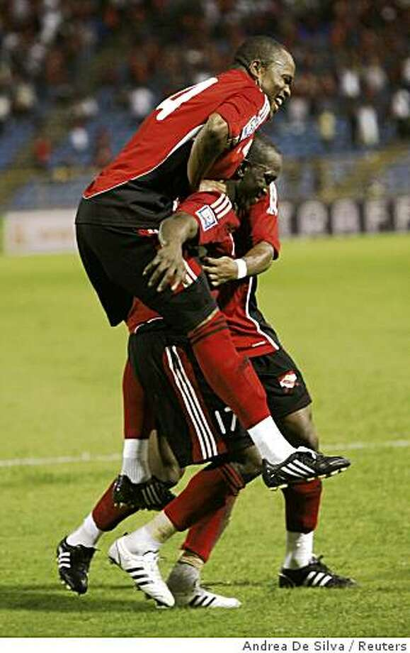 Trinidad and Tobago's Dwight Yorke is congratulated by Stern John (top) after scoring the second goal against the U.S. during their 2010 World Cup qualifier soccer match at the Hasely Crawford Stadium, in Port of Spain, Trinidad on October 15, 2008. Photo: Andrea De Silva, Reuters