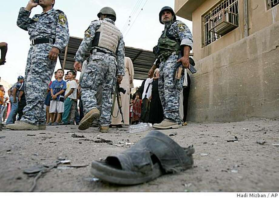 A shoe of one of the victims, is seen, on the ground as Iraqi forces stand guard the area after a car bomb explosion in the predominantly Shiite Bayaa district, southwestern Baghdad, iraq, on Sunday, Oct. 12, 2008. The bomb exploded Sunday in a commercial street of Baghdad killing seven people and wounding nine others, police said. (AP Photo/Hadi Mizban) Photo: Hadi Mizban, AP