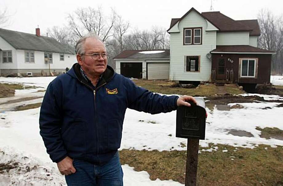 In this March 9, 2010 photo, Chelsea, Iowa Mayor Roger Ochs stands in front of a flood-damaged home that was unable to be saved in Chelsea, Iowa. Chelsea's 297 residents were tempted to move after 2008's flood but ultimately opted to stay put. Municipal leaders considered a plan to move their town, in the northern part of the state between the Iowa River and Otter Creek, to a nearby hill. But the plan was scrapped when the farmer who owned the land decided not to sell. Photo: Conrad Schmidt, AP