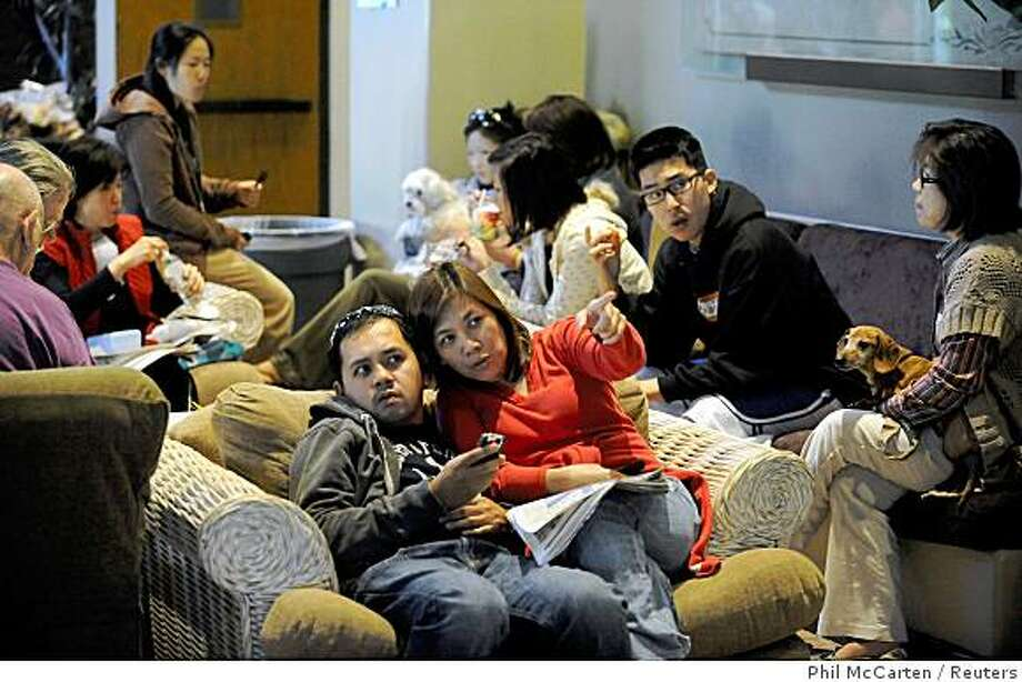Residents Eric Francisco (L) and wife Shirley Francisco watch a news broadcast of the fire with other evacuees  while firefighters work to contain a wildfire in the Porter Ranch area of Los Angeles October 14, 2008. REUTERS/Phil McCarten (UNITED STATES) Photo: Phil McCarten, Reuters