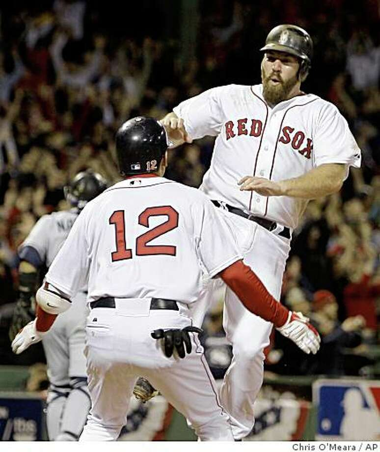 Boston Red Sox's Kevin Youkilis, right, leaps into Jed Lowrie's arms as he scores the winning run on an RBI single by J.D. Drew in the eighth inning in Game 5 of the American League baseball championship series in Boston, Thursday, Oct. 16, 2008. The Red Sox defeated the Tampa Bay Rays 8-7. (AP Photo/Chris O'Meara) Photo: Chris O'Meara, AP