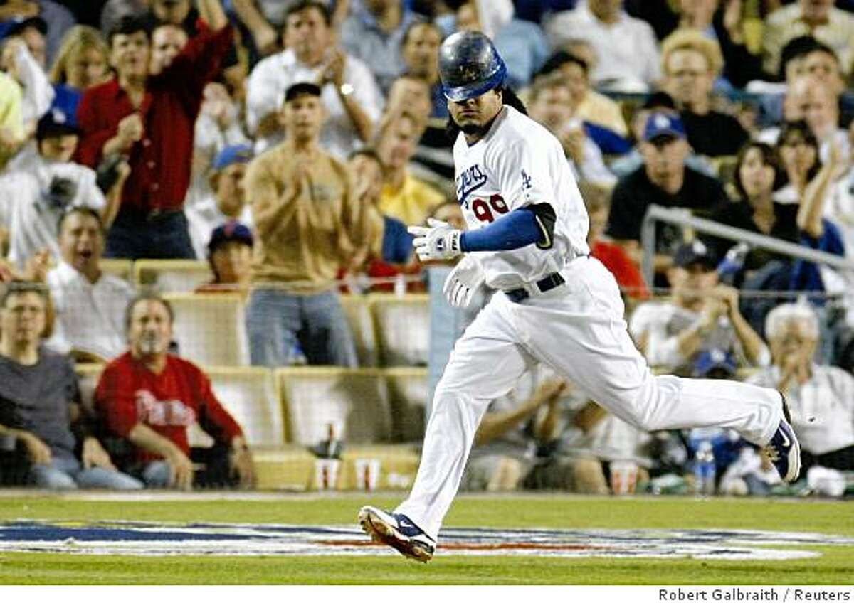 Los Angeles Dodgers' Manny Ramirez loses his helmet as he runs to first base on a single n the eighth inning against the Philadephia Phillies in Game 5 of Major League Baseball's NLCS playoff series in Los Angeles, October 15, 2008. REUTERS/Robert Galbraith (UNITED STATES)