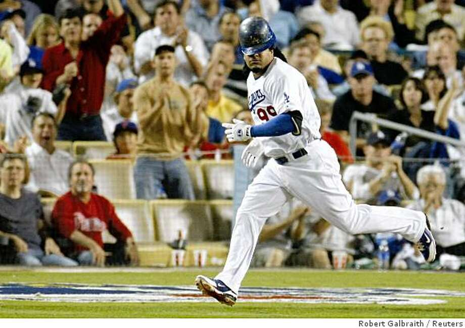 Los Angeles Dodgers' Manny Ramirez loses his helmet as he runs to first base on a single n the eighth inning against the Philadephia Phillies in Game 5 of Major League Baseball's NLCS playoff series in Los Angeles, October 15, 2008.     REUTERS/Robert Galbraith (UNITED STATES) Photo: Robert Galbraith, Reuters