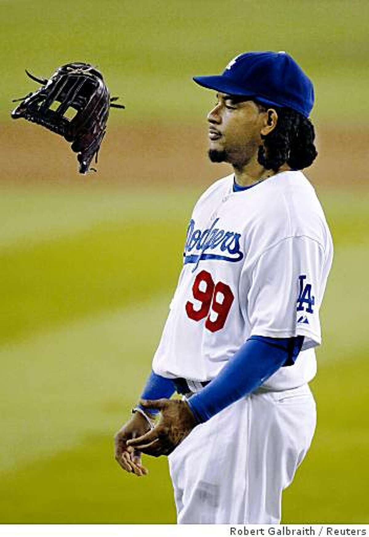 Los Angeles Dodgers left fielder Manny Ramirez flips his glove during a pitching change in the eighth inning against the Philadephia Phillies in Game 5 of Major League Baseball's NLCS playoff series in Los Angeles, October 15, 2008. REUTERS/Robert Galbraith (UNITED STATES)