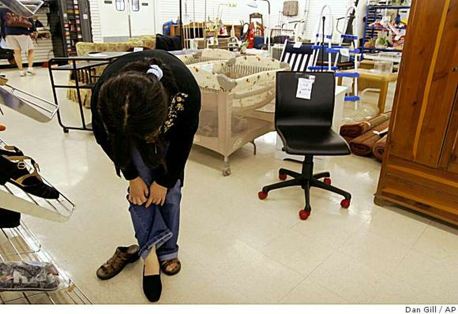 Eon Ju Jeon of Columbia, Mo. shops for a funeral outfit at a Goodwill store, Wednesday, Sept. 24, 2008, in Columbia, Mo. (AP Photo/Dan Gill) Photo: Dan Gill, AP