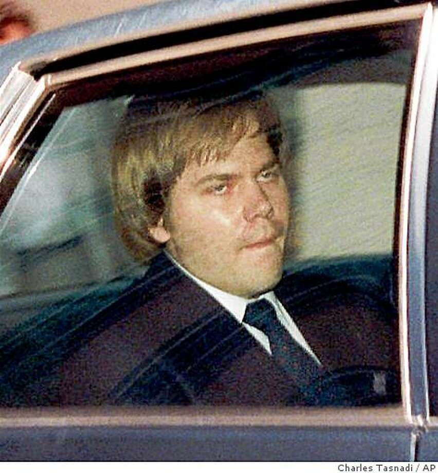 John Hinckley Jr. is escorted from U.S. District Court in Washington in this April 13, 1987 file photo. A divided appeals court panel cleared the way Friday, Jan. 15, 1999 for Hinckley to make supervised day trips away from the mental hospital where he has been confined since he tried to assassinate former President Reagan. (AP Photo/Charles Tasnadi) Photo: Charles Tasnadi, AP