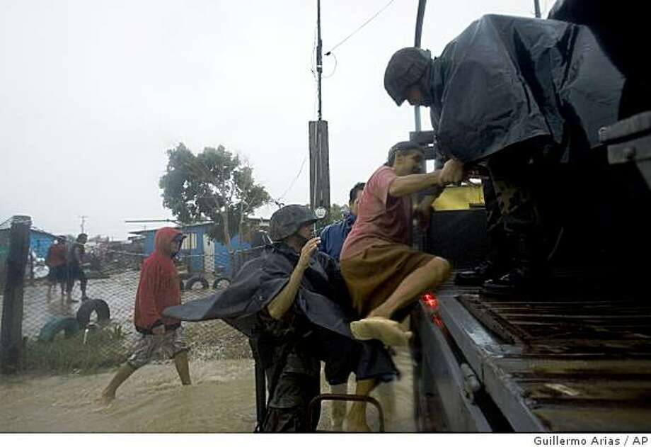 Mexican marines help a woman to get into a truck during Hurricane Norbert in Puerto San Carlos, Mexico, Saturday, Oct. 11, 2008. Hurricane Norbert slammed into Mexico's southern Baja California peninsula with torrential rains and screaming winds, forcing scores of people to flee flooded homes. (AP Photo/Guillermo Arias) Photo: Guillermo Arias, AP