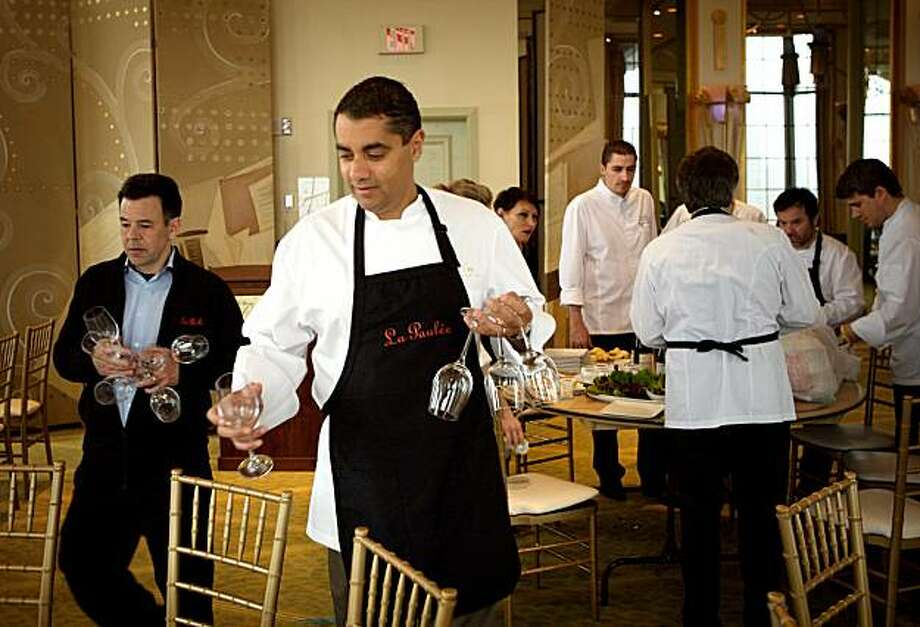 Michael Mina, chef of Mina restaurant, (center) passes out wine glasses as he prepares for lunch on a break in preparation for La Paulée San Francisco a dinner held at the Westin St. Francis, March 12, 2010. Photo: Thor Swift, Special To The Chronicle