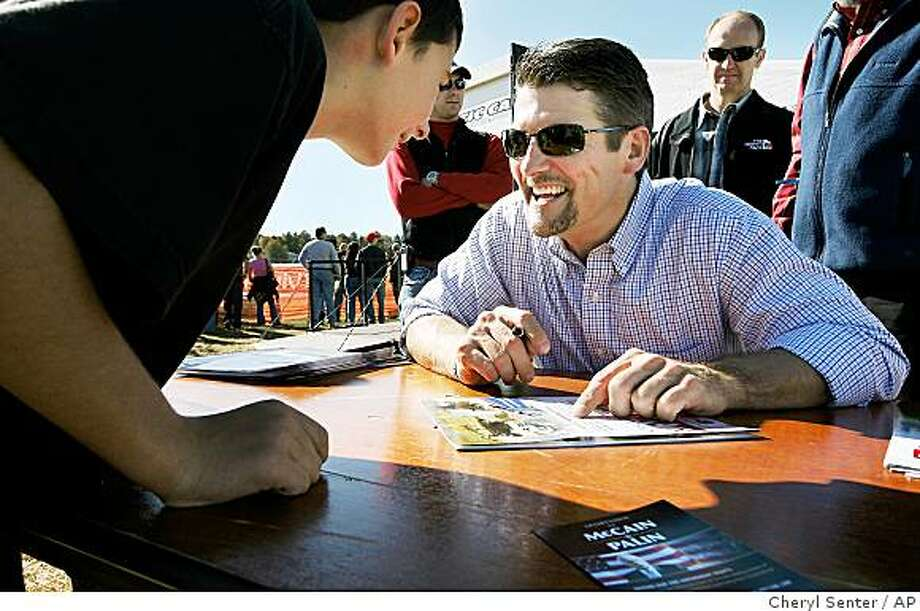 Todd Palin husband of Republican vice presidential candidate Alaska Gov. Sarah Palin, signs an autograph for 10-year-old Jim Doherty, left, of Arlington, Mass, at the Grass Drags and Water Crossing snowmobile event in Fremont, N.H., Saturday, Oct. 11, 2008. (AP Photo/Cheryl Senter) Photo: Cheryl Senter, AP