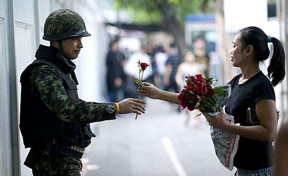 BANGKOK, THAILAND - APRIL 30: A Bangkok resident hands a soldier a rose in appreciation as he stands guard on Convent Road in Bangkok on April 30, 2010 in Thailand. Soldiers and police are deployed throughout the city. The anti-government protest that hasclosed much of central Bangkok's commercial district is now in its seventh week. Photo: Andy Nelson, Getty Images
