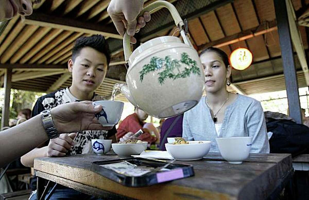 Hashim Aosafwani pours tea for Tony Vang (left) and Zahra Aosafwani during a visit to the Japanese Tea Garden at Golden Gate Park in San Francisco, Calif. on Wednesday Oct. 15, 2008.