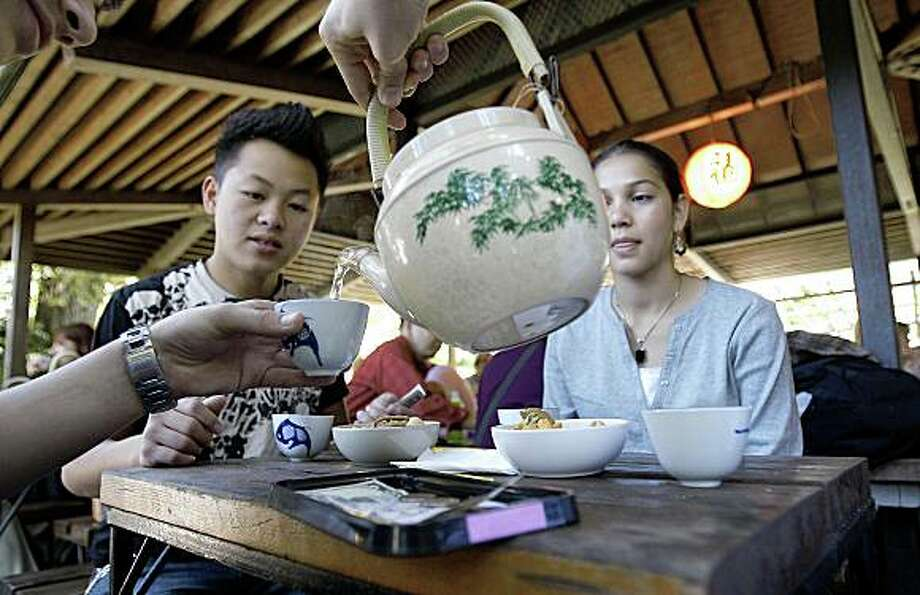 Hashim Aosafwani pours tea for Tony Vang (left) and Zahra Aosafwani during a visit to the Japanese Tea Garden at Golden Gate Park in San Francisco, Calif. on Wednesday Oct. 15, 2008. Photo: Michael Macor, The Chronicle