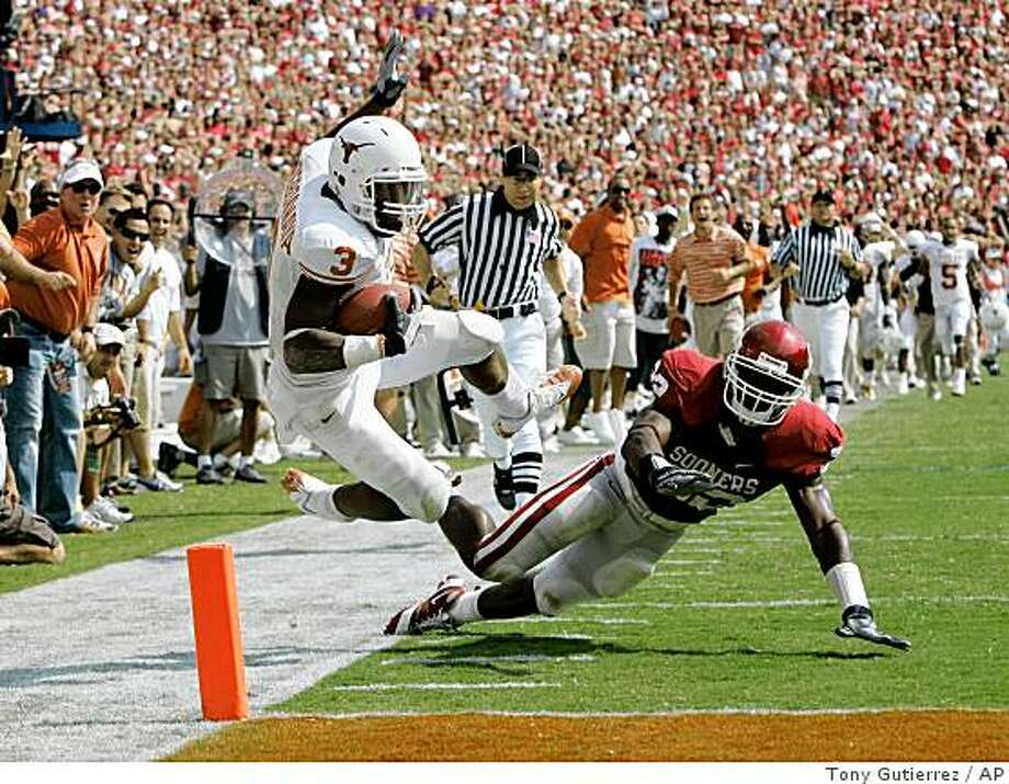 Texas running back Chris Ogbonnaya (3) is knocked out-of-bounds by Oklahoma linebacker Keenan Clayton (22) after a 62-yard run to the two yard line in the fourth quarter during an NCAA college football game, Saturday, Oct. 11, 2008, in Dallas. The play set up a Texas score in their 45-35 win. (AP Photo/Tony Gutierrez) Photo: Tony Gutierrez, AP