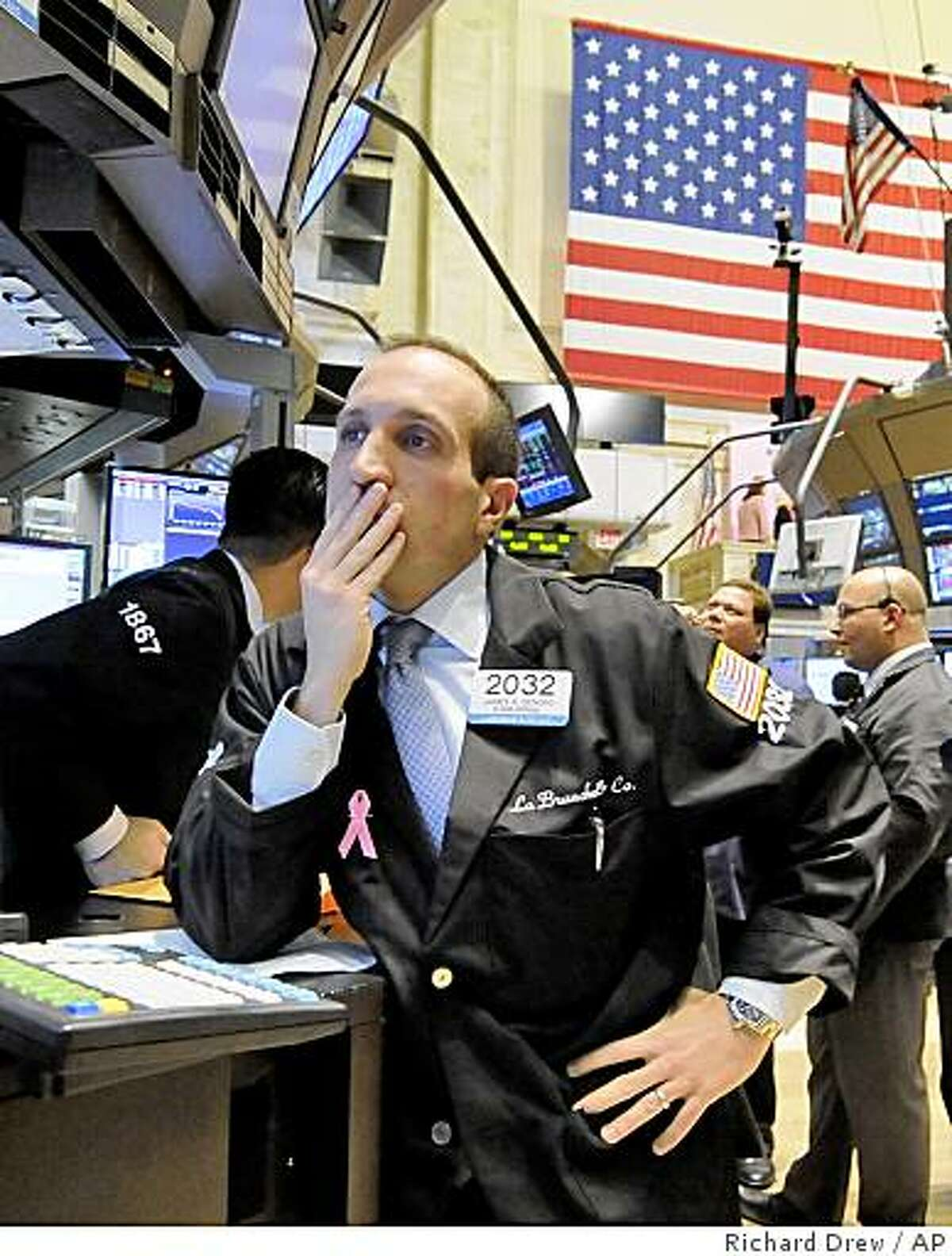 Specialist James Denaro, left, works at his post on the floor of the New York Stock Exchange after the closing bell, Friday, Oct. 10, 2008. Wall Street capped its worst week ever with a wild session Friday that saw the Dow Jones industrials rocket within a 1,000 point range before closing with a relatively mild loss and the Nasdaq composite index actually end with a modest advance. (AP Photo/Richard Drew)