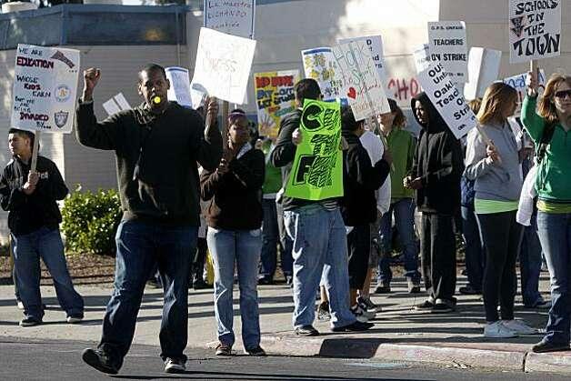 Teacher at oakland hight school leads a picket outside the school