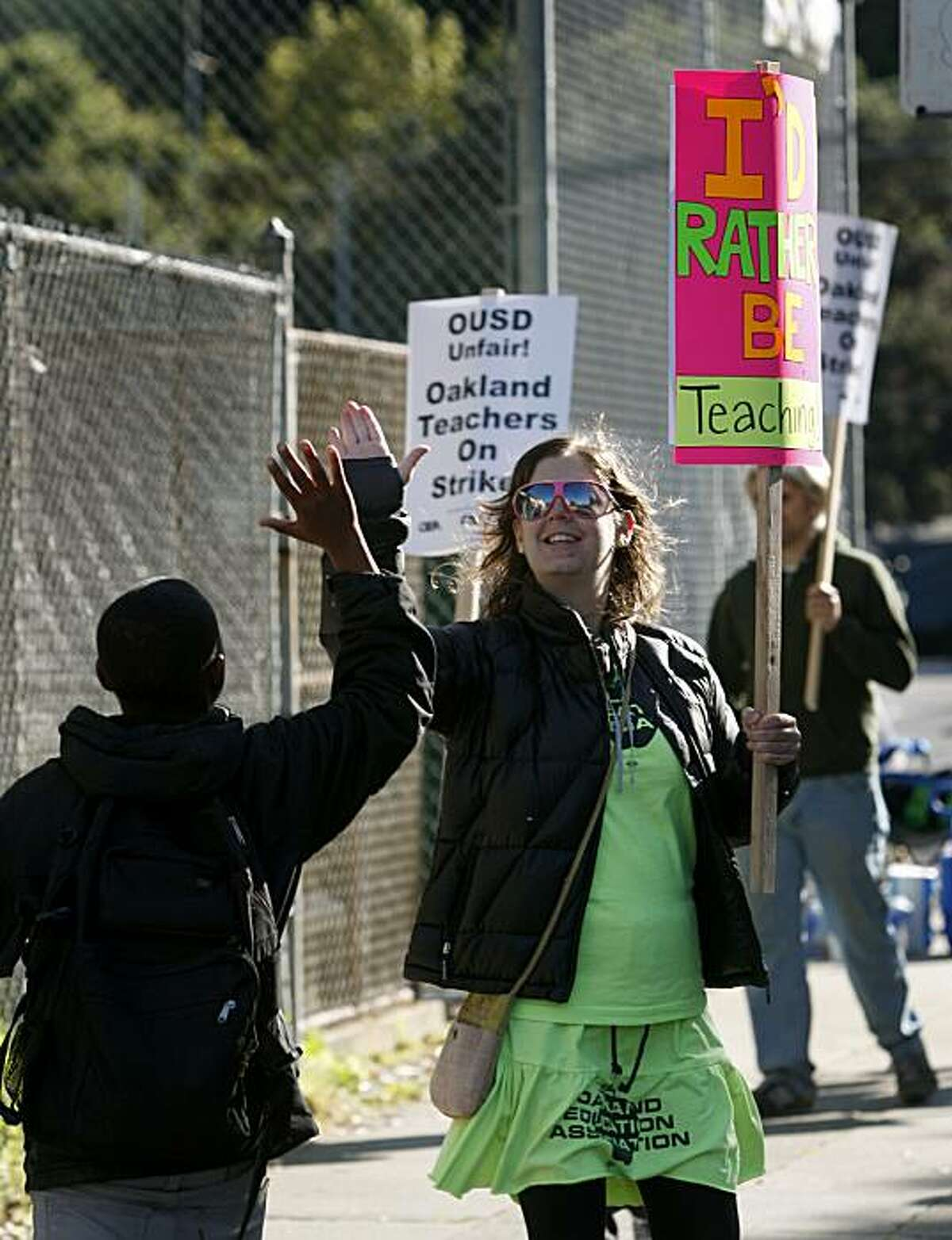 Jessie Thaler (right) who teaches English at Claremont Middle School, high-fives a student arriving for class during the one-day walkout by teachers in Oakland, Calif., on Thursday, April 29, 2010. School teachers are protesting district-wide cuts in pay and programs.