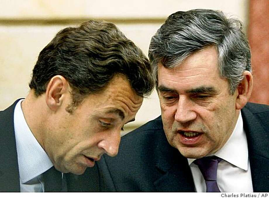 British Prime Minister Gordon Brown, right, speaks to French President Nicolas Sarkozy, left, during the financial crisis summit gathering Eurogroup heads of state and government at the Elysee Palace in Paris Sunday, Oct. 12, 2008. Countries that use the euro will temporarily guarantee future bank debt to encourage lending and ease the credit crunch, according to a draft statement under discussion by European leaders Sunday. (AP Photo/Charles Platiau, Pool) Photo: Charles Platiau, AP