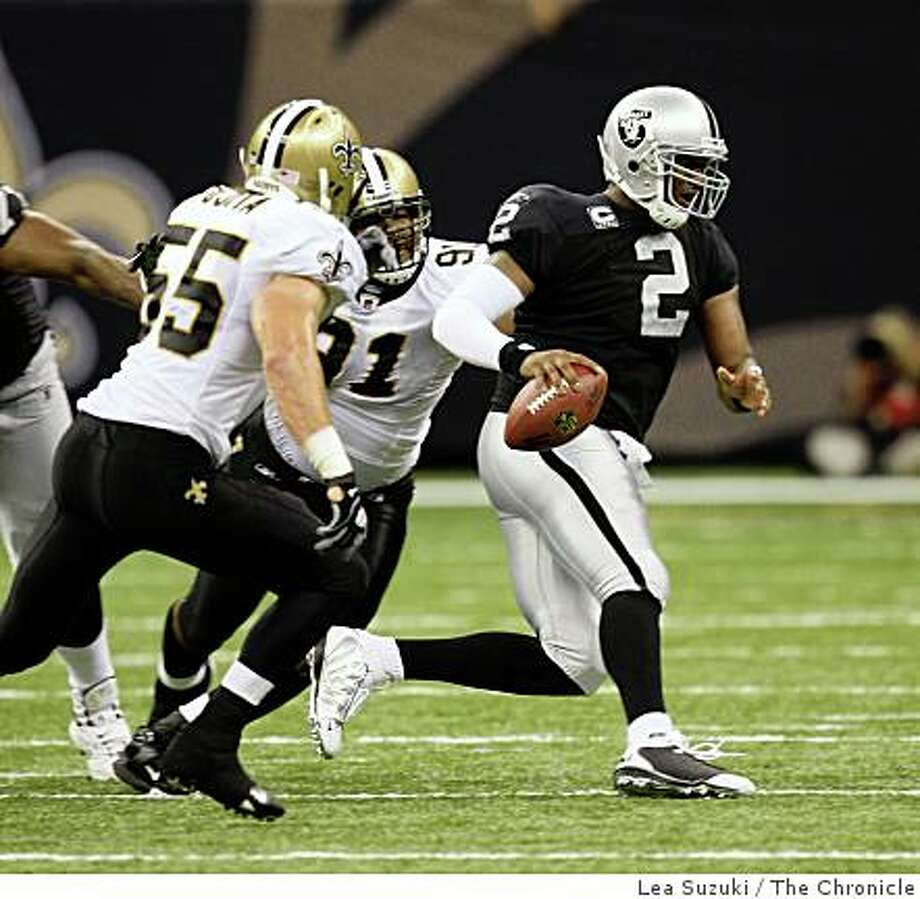 Oakland Raiders Quarterback JaMarcus Russell (2) (right) tries to evade New Orleans Saints Will Smith (91) (second from right) who gets a hand on him during the second half of the Oakland Raiders  vs. New Orleans Saints game at the New Orleans Superdome on Sunday, October 12, 2008 in New Orleans, La.  Final Score: Oakland Raiders: 3 -  New Orleans Saints: 34 Photo: Lea Suzuki, The Chronicle
