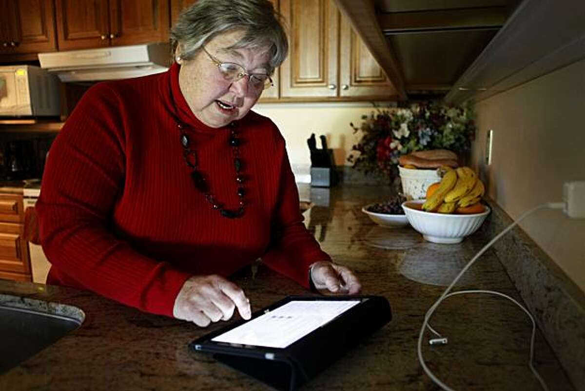 Rita Schena, 78, checks email on her new iPad at her home on Thursday April 29, 2010 in Menlo Park, Calif. Schena said she is very excited to have this device and feels its perfect for seniors on the go.