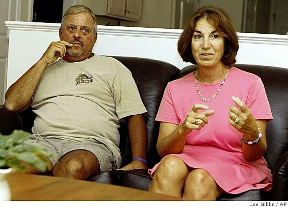 Christopher Burke listens as his wife Ann talks about the implementation of the Lindsay Burke law in Rhode island public schools at their home in North Kingstown, R.I. on Monday, Sept. 22, 2008. The Burke's daughter, Lindsay, was murdered by her boyfriend in 2005 after an abusive relationship. A new law, named in Lindsay's honor, mandates education of students and faculty in Rhode Island public schools about the signs of an abusive relationship.  (AP Photo/Joe Giblin) Photo: Joe Giblin, AP