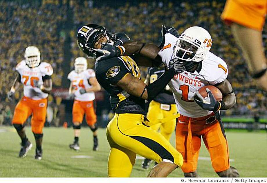 COLUMBIA, MO - OCTOBER 11:  Dez Bryant #1 of the Oklahoma State Cowboys stiff-arms Castine Bridges #21 of the Missouri Tigers  on October 11, 2008 at Memorial Stadium in Columbia, Missouri.  (Photo by G. Newman Lowrance/Getty Images) Photo: G. Newman Lowrance, Getty Images