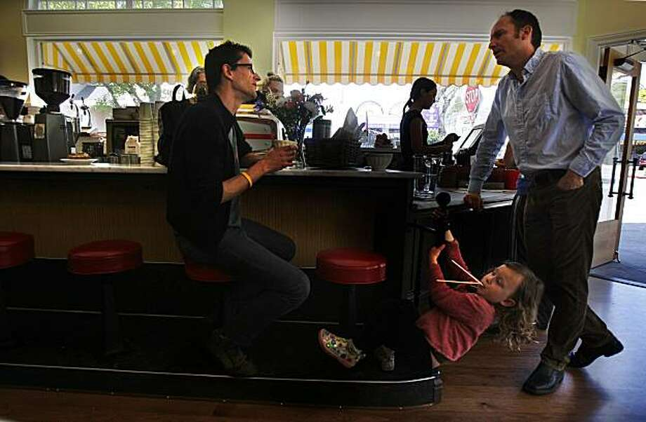 Pedro Murteira (left) having a cappucino while talking with owner Michael Pearce (right) as Sophia Murteira (middle), 3 years old, plays at Elmwood Cafe in Berkeley, Calif., on Friday, April 23, 2010. Photo: Liz Hafalia, The Chronicle