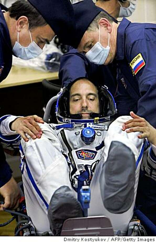 US space tourist Richard Garriott is helped putting on his space suit at the Baikonur cosmodrome, in Kazakhstan, on October 12, 2008. US space tourist Richard Garriott is set to blast off for the International Space Station (ISS) aboard a Soyuz TMA-13 rocket from the Baikonur cosmodrome with Michael Fink of the US and Russia's Iouri Lonchakov on October 12. AFP PHOTO / DMITRY KOSTYUKOV (Photo credit should read DMITRY KOSTYUKOV/AFP/Getty Images) Photo: Dmitry Kostyukov, AFP/Getty Images