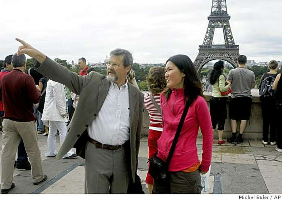 In this photo taken on Aug. 8, 2008 in Paris, Christian Ragil of France, left, guides Ju Young Gam of South Korea, as they tour the Trocadero plaza near the Eiffel tower, seen behind. The city of light has an unfortunate blight: the locals' reputation for rudeness. That's why a group of friendly Parisians have banded together to show complete strangers around their Paris, the one not found in travel books, for free. (AP Photo/Michel Euler) Photo: Michel Euler, AP