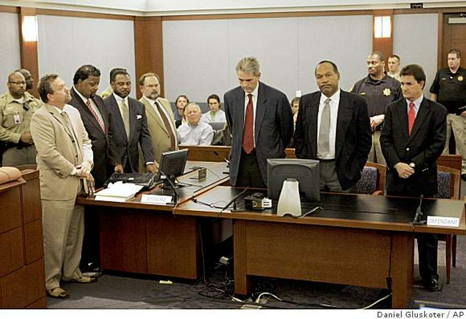 """** FILE ** Co-defendants Clarence """"C.J."""" Stewart and O. J. Simpson, second from right standing, and their defense teams listen as the two are found guilty on all 12 charges, including felony kidnapping, armed robbery and conspiracy at the Clark County Regional Justice Center in Las Vegas, Friday, Oct. 3, 2008. The verdict comes 13 years to the day after he was acquitted of double murder charges. (AP Photo/Daniel Gluskoter, Pool) Photo: Daniel Gluskoter, AP"""