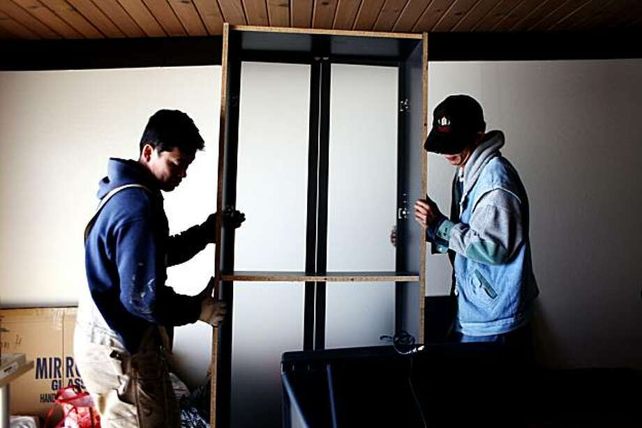 Jan Chen (left) and Eric Zheng (right) were sent over by the landlord at 320 Esplanade Ave. in Pacifica to help residents ordered to evacuate their apartments on Friday. Photo: Jessica Pons, The Chronicle