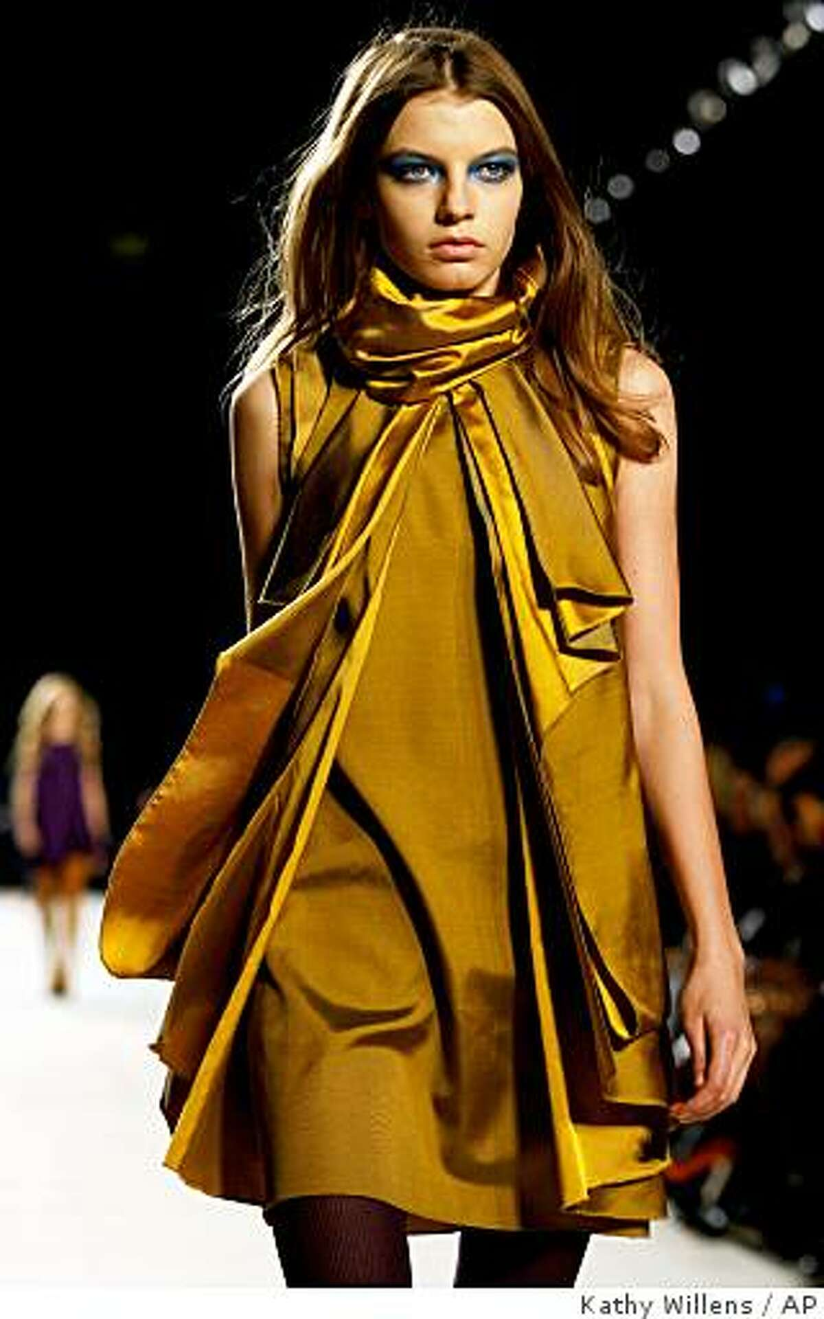 **FILE** A model walks the runway during the presentation of Proenza Schouler's Fall 2008 collection in New York in this Monday, Feb. 4, 2008 file photo. Mustard yellow, as seen here, is among the muted colors common at Fall Fashion Week. (AP Photo/Kathy Willens, FILE)
