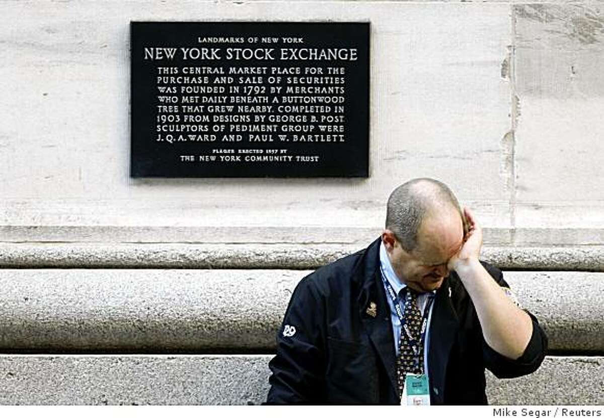A weary trader rubs his eyes as he pauses outside the New York Stock Exchange following the end of the trading session in New York October 9, 2008. The Dow Jones Industrial Average dropped 678.91 points on the day to finish at 8579.19 closing below 9,000 for the first time since 2003. REUTERS/Mike Segar (UNITED STATES)