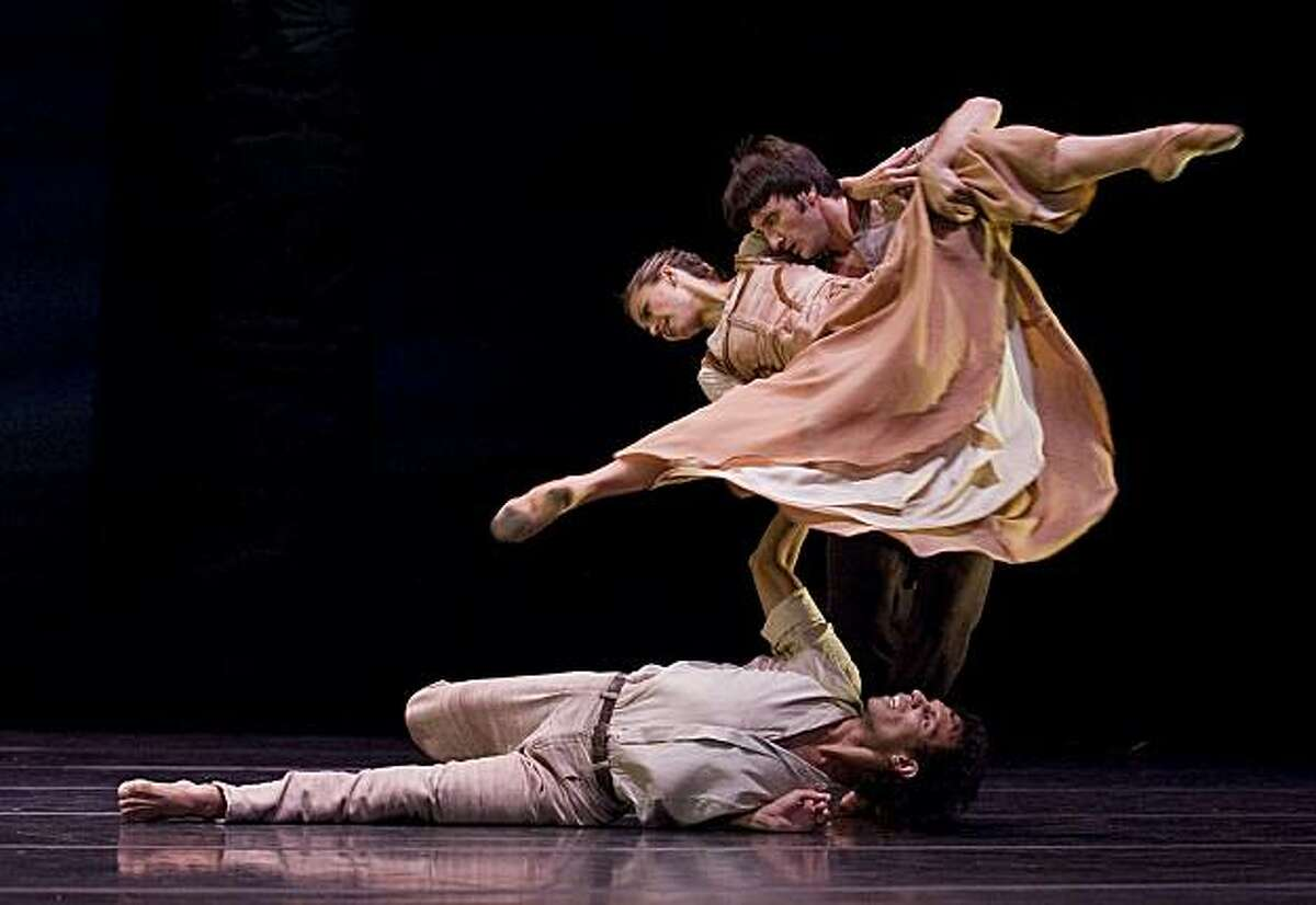 """Francisco Lorenzo (on floor), Africa Maria Gúzman (woman), and Gentian Doda (lifting her) dance in """"Arenal,"""" one of three works on the program for Compañía Nacional de Danza, presented by San Francisco Performances April 29-May 1 at Novellus Theater at Yerba Buena Center for the Arts./CREDIT: Fernando Marcos"""