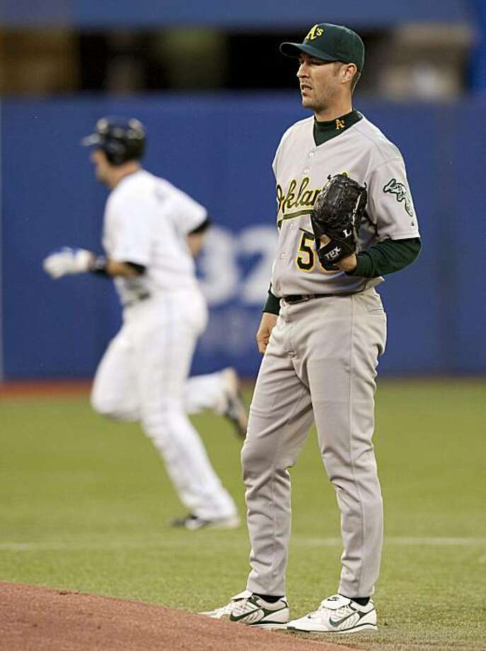 ** CORRECTS YEAR TO 2010 NOT 2009 ** Oakland Athletics starting pitcher Justin Duchscherer, foreground, stands by the mound as Toronto Blue Jays' John Buck rounds the bases after hitting his first home run of two in third-inning baseball game action in Toronto on Thursday, April 29, 2010. Photo: Frank Gunn, AP