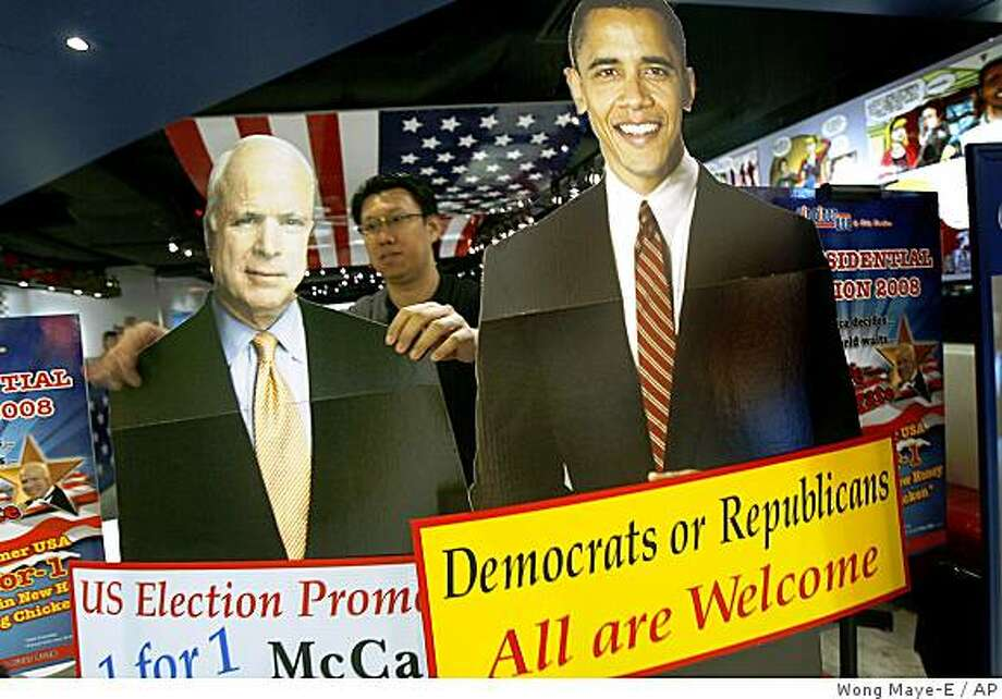 An American restaurant staff adjusts life-sized standees of U.S. presidential candidates as part of their lunch promotion advertisements banking on the U.S. presidential campaign fever to promote their outlet on Friday, Oct. 10, 2008, in Singapore. Republican John McCain on Thursday intensified character attacks on Democratic opponent Barack Obama, who is climbing in the polls as voters' preferred candidate to handle a deepening financial crisis and plunging stock market. (AP Photo/ Wong Maye-E) Photo: Wong Maye-E, AP