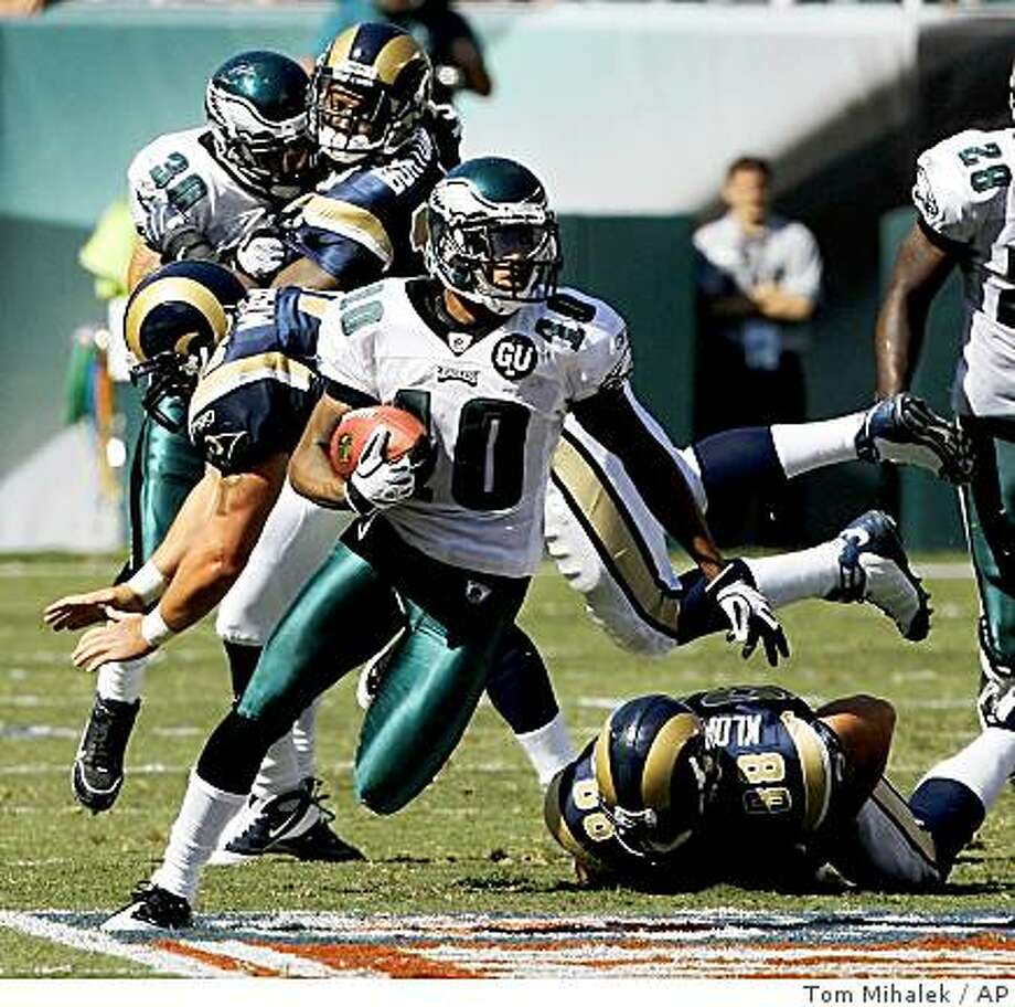 Philadelphia Eagles' wide receiver/punt-returner DeSean Jackson, foreground, eludes tackles by the St. Louis Rams' Chris Massey (airborne) and Joe Klopfenstein (88) while running the ball for 60 yards in the third quarter of an NFL football game, Sunday, Sept. 7, 2008, in Philadelphia.  Jackson, the first Eagles rookie wide receiver to start the season-opener in 18 years, had six catches for 106 yards in the Eagles' 38-3 win. (AP Photo/Tom Mihalek) Photo: Tom Mihalek, AP