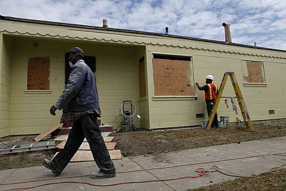 Employees from Turner Group Construction prepare a house for painting. Photo: Mike Kepka, The Chronicle