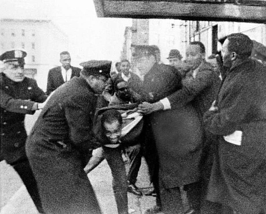 In this Feb. 21, 1965 file photo released by WCBS-TV, Thomas Hagan, 22, struggles with police who take him from the scene outside the ballroom where Malcolm X was shot and killed in New York. Hagan, the last man still serving time in the 1965 killing, was freed on parole Tuesday, April 27, 2010,  from a Manhattan prison where he spent two days a week under a work-release program.  Hagan, 69, has said he was one of three gunmen who shot Malcolm X as he began a speech at Harlem's Audubon Ballroom. Photo: Wcbs-tv, AP