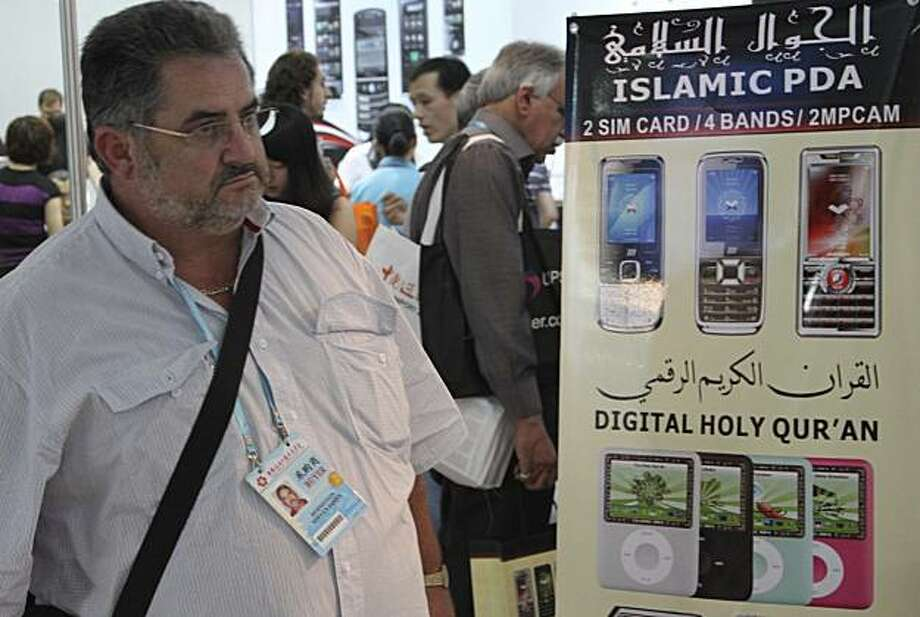 In this photo taken Friday, Oct. 16, 2009, a man walks past an advertisement board featuring fake iPods at the Canton Fair in Guangzhou, south China's Guangdong province. Thousands of foreigner buyers flock to the southern city of Guangzhou at this time of year for China's biggest trade show. (AP Photo/William Foreman) Photo: William Foreman, AP
