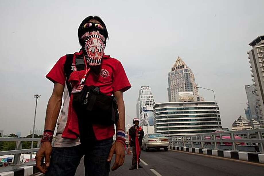 BANGKOK, THAILAND - APRIL 24:  One of the anti-government 'Red Shirt' protesters watches traffic go by, guarding a lookout point on a bridge overlooking the redshirt camp April 24, 2010 in Bangkok, Thailand. Thailand's political crisis plunged back into deadlock today after the government rejected a compromise offer from red-shirted demonstrators who said they were now braced for a crackdown. Photo: Paula Bronstein, Getty Images