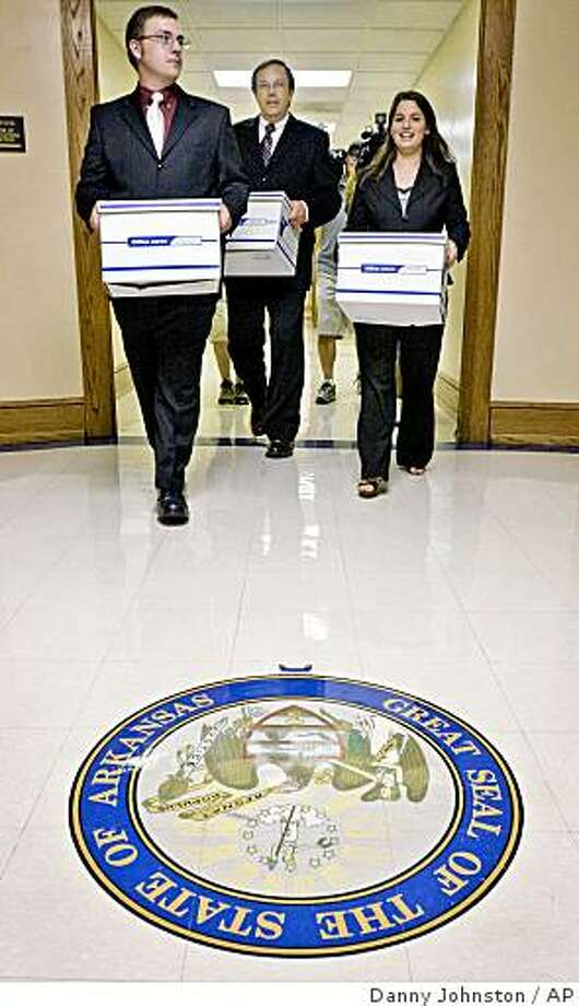 ** FILE ** In this Thursday, Aug. 21, 2008 file photo, David Cox, left, and Jill Davis, right, carry boxes of petitions with Arkansas Family Council Action Committee President Jerry Cox, center, at the Arkansas state Capitol in Little Rock, Ark. Children's advocacy groups are fighting Arkansas' policy barring unmarried couples living together from fostering children, as a campaign is under way to put a similar restriction into law. (AP Photo/Danny Johnston) Photo: Danny Johnston, AP