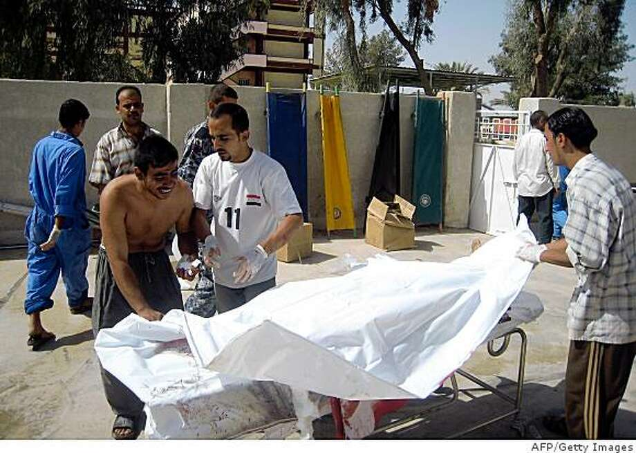 An Iraqi man weeps over the body of a relative as hospital workers identify and cover bodies of victims of a suicide bombing on October 8, 2008 outside a hospital of the restive Iraqi city of Baquba, some 60 kilometres (37 miles) north of Baghdad. A woman suicide bomber blew herself up outside Baquba's courthouse, killing six security personnel and three civilians, officials and witnesses said. Today's attack was the worst suicide bombing in three weeks in the Diyala province, one of the most dangerous areas in Iraq.  AFP PHOTO / STR (Photo credit should read -/AFP/Getty Images) Photo: -, AFP/Getty Images