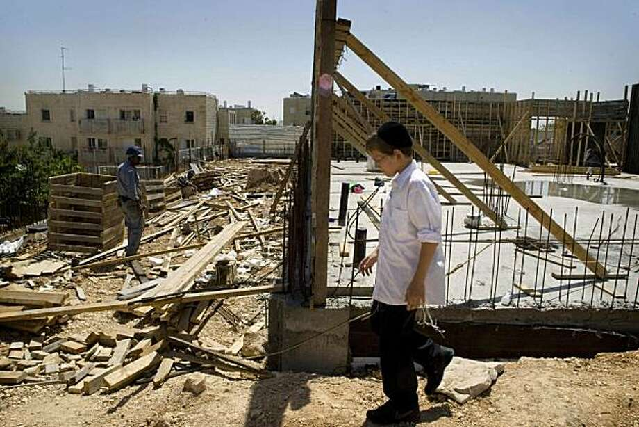 An Ultra-orthodox Jewish boy walks past a construction site in the east Jerusalem neighborhood of Ramat Shlomo, Monday, April 26, 2010. Under heavy U.S. pressure, Israel's Prime Minister Benjamin Netanyahu has imposed a de facto freeze on new Jewish construction in disputed east Jerusalem despite his declarations to the contrary, city officials said Monday, a move likely to enrage hardline supporters but advance U.S.-backed Mideast peace efforts. Photo: Sebastian Scheiner, AP
