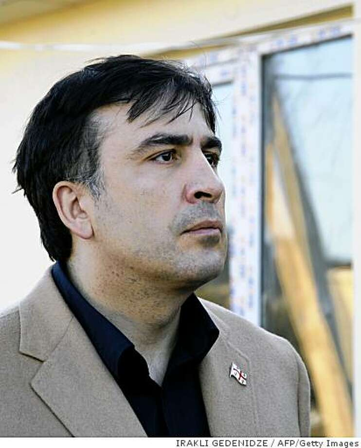 Georgian President Mikheil Saakashvili  examines plans for a settlement to be built for refugees 20 km west of Tbilisi in the town of Tserovani on October 6, 2008. Forces in Georgia are seeking to trigger fresh military action around the country's separatist regions, Russia said Monday, despite stressing it would complete a scheduled troop pull-back on time.                 AFP PHOTO / POOL / IRAKLI GEDENIDZE (Photo credit should read IRAKLI GEDENIDZE/AFP/Getty Images) Photo: IRAKLI GEDENIDZE, AFP/Getty Images