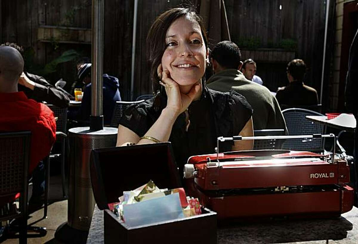 San Francisco poet Silvi Alcivar sitting in the patio area of Atlas Cafe, ready to do poetry on demand with her typewriter and box of paper in San Francisco, Calif., on Wednesday, April 21, 2010.