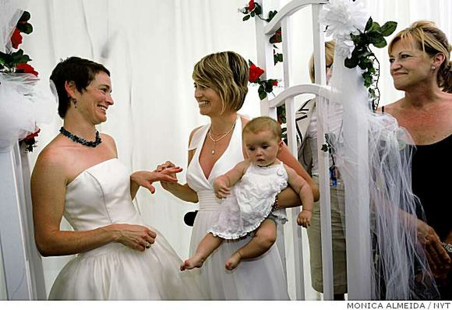 (NYT25) WEST HOLLYWOOD, Calif. -- June 17, 2008 -- CALIF-GAY-MARRIAGE-8 --  Tori, left, and Kate Kuykendall, with daughter Zadia, after their wedding ceremony in West Hollywood, Calif., on Tuesday, June 17, 2008.  With a quiet pride and a sense of history, hundreds of gay and lesbian couples across California wed on Tuesday, giving a human face to a landmark court decision and a powerful opening salvo in what is expected to be a bruising fall campaign here over the issue of same-sex marriage. (Monica Almeida/The New York Times) Photo: MONICA ALMEIDA, NYT