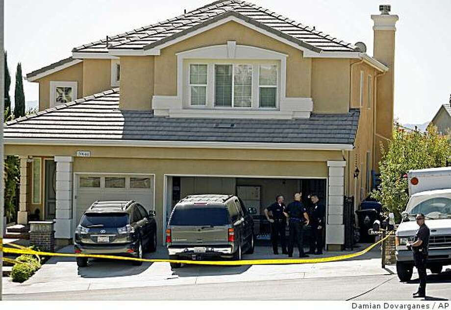 Los Angeles Police officers stand in front of the home where six  bodies were found at a gated community in the San Fernando Valley neighborhood of Porter Ranch area of Los Angeles on Monday, Oct. 6, 2008. An unemployed accounting industry worker who was despondent over financial problems shot and killed his wife, three children, mother-in-law and then himself in an upscale home in a gated community, police said Monday. (AP Photo/Damian Dovarganes) Photo: Damian Dovarganes, AP