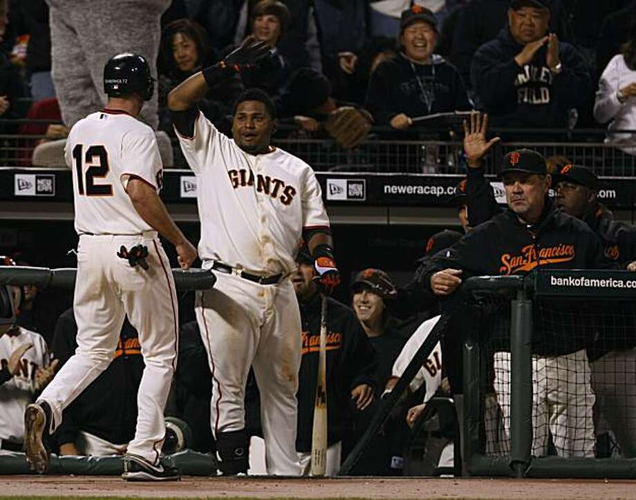 Nate Schierholtz is greeted in the dugout by Pablo Sandoval after scoring the go-ahead run for the San Francisco Giants in the eighth inning against the St. Louis Cardinals in San Francisco on Saturday. Photo: Paul Chinn, The Chronicle