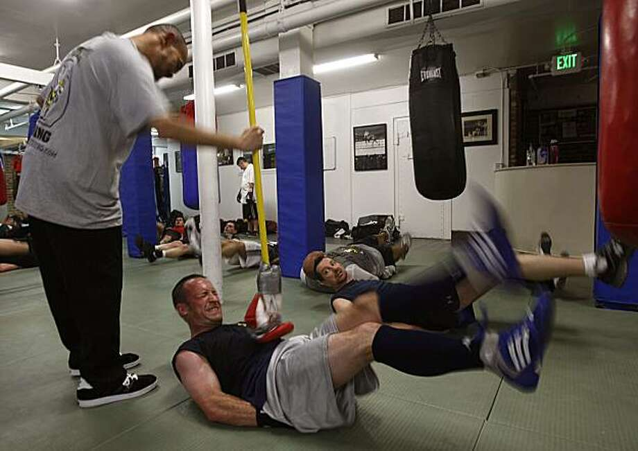 Louis Bachleder, 33 years old, is doing a timed leg lift as trainer Eddie Croft uses a boxing glove on a stick  to make sure those abs are being used at B Street Gym in San Mateo, Calif., on Thursday, March 18, 2010.  Bachleder took up boxing a year ago to get  in shape for the SF Firefighter's exam. Photo: Liz Hafalia, The Chronicle